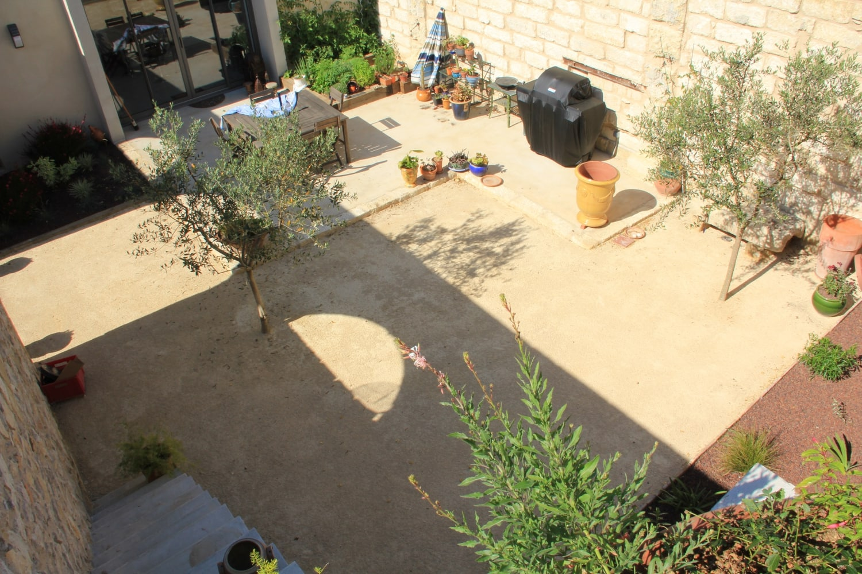terrasse en béton lissé marius aurenti et bordures en pierre pour aménager cette cour extérieure